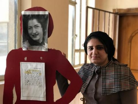 Kaiy standing next to a picture of Sabiha Shaikh Dawood, an Iraqi woman and the first female judge in the Arab world. The text in the picture reads: Sabiha Shaikh Dawood (1912-1975) was one of the first female