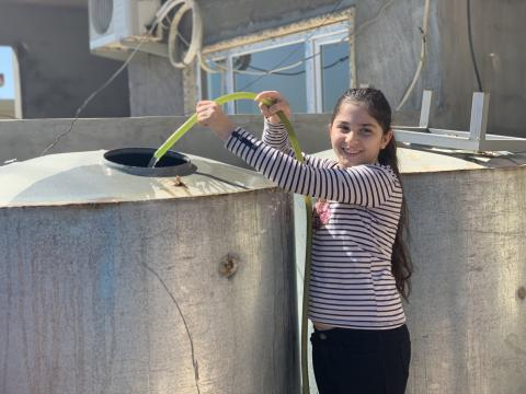 Ronak smiles as she pours water into one of the water tanks at her home in Bartella, east of Mosul