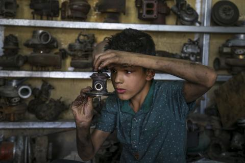 Karrar, 14, works at a car repair shop in Baghdad