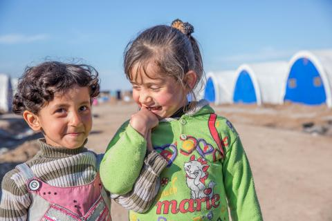 Four-year-olds Sidra and Asha hold hands in a camp for displaced people in Iraq