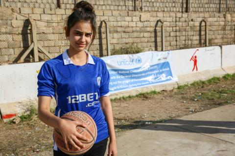 "Nabaa, 17, holds a basketball before a game at Al-Yaqatha High School in Kirkuk's Arafa District.   ""I love playing basketball,"" she says. ""I am following in my father's footsteps. He was also a basketball player."""