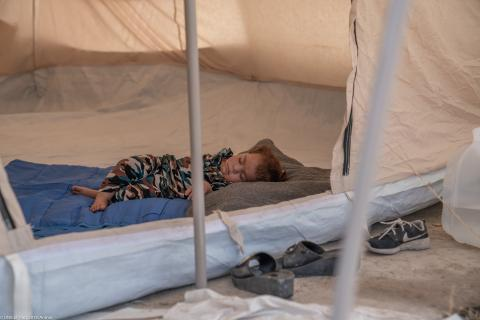 A child sleeps in a tent at Badarash camp, Iraq