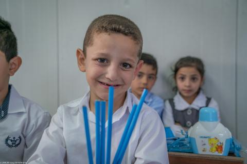A child is sitting in a classroom holding lots of pencils.