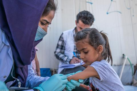 A girl receives a vaccination against polio and measles after fleeing the conflict in Syria