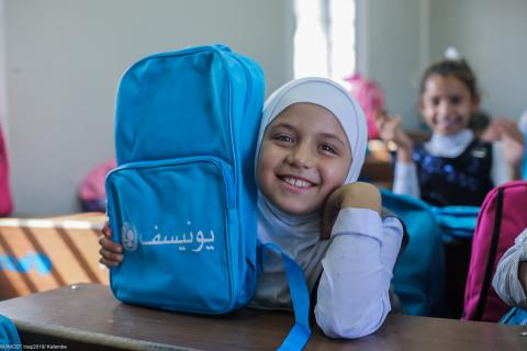 A girl is sitting in a classroom feeling happy because she got UNICEF school bag