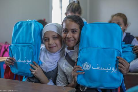 Two girls hold their new backpacks after a UNICEF distribution of learning materials