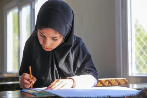 A girl writes in a book in Iraq