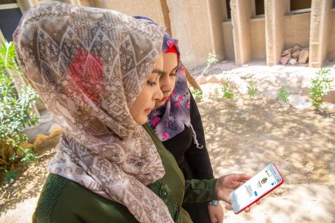 Young girls go through a phone showing the Ureport Iraq page
