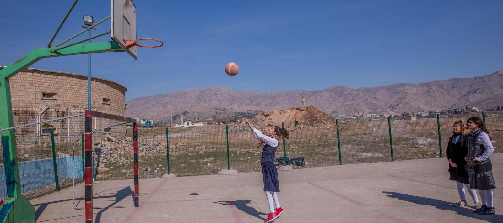 A Syrian girl is playing basketball