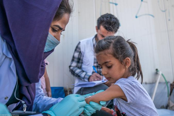 A girl receives an immunisation shot at Badarash camp, Iraq