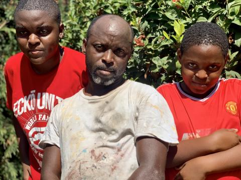 Father Ian 'Cowfoot' Salmon together with his two sons Jevontae, aged 16 (left) and Devontae, aged 13 in their community of Mountain View, St Andrew.