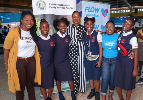 Photograph of Terri-Karelle Reid (centre), UNICEF U-Report Youth Council member Danielle Mullings (left) and National Secondary Schools Council (NSSC) representative Isheba Cornwall (second right), with students at a FLOW Foundation Safer Internet Day event at Merl Grove High School.