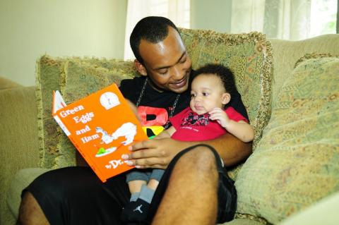 Photograph of a father reading to his child