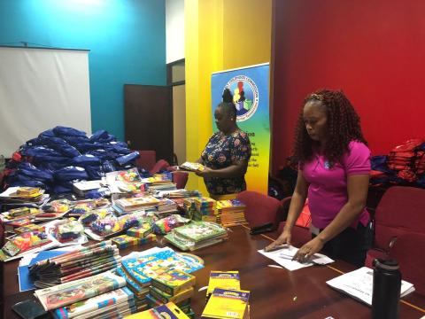 Photograph of workers from the Early Childhood Commission and Food for the Poor packing the learning kits.