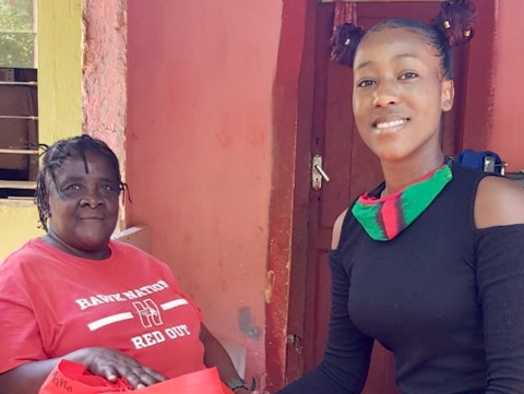 Photograph of Akela Phillips delivering items to support residents during COVID-19 in her home community of 8 Miles, St Ann.
