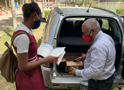 Texal Christie, Principal of Kellits High School, delivering text books to a student