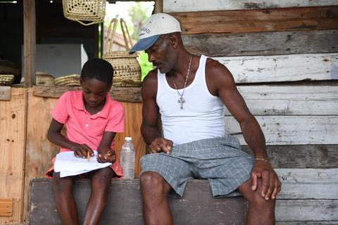 Joel Young a student of Little Bay Primary and Infant School with his father Wayne Young a fisherman. going through the weeks lessons. The school is located in Little Bay, a mainly fishing community located in the parish of Westmoreland, the western end of the island of Jamaica on Monday, September 7, 2020.
