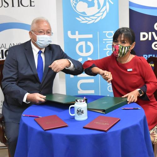 Minister of Justice Delroy Chuck and UNICEF Jamaica Country Representative Mariko Kagoshima signing a document to increase support for the national child diversion programme.