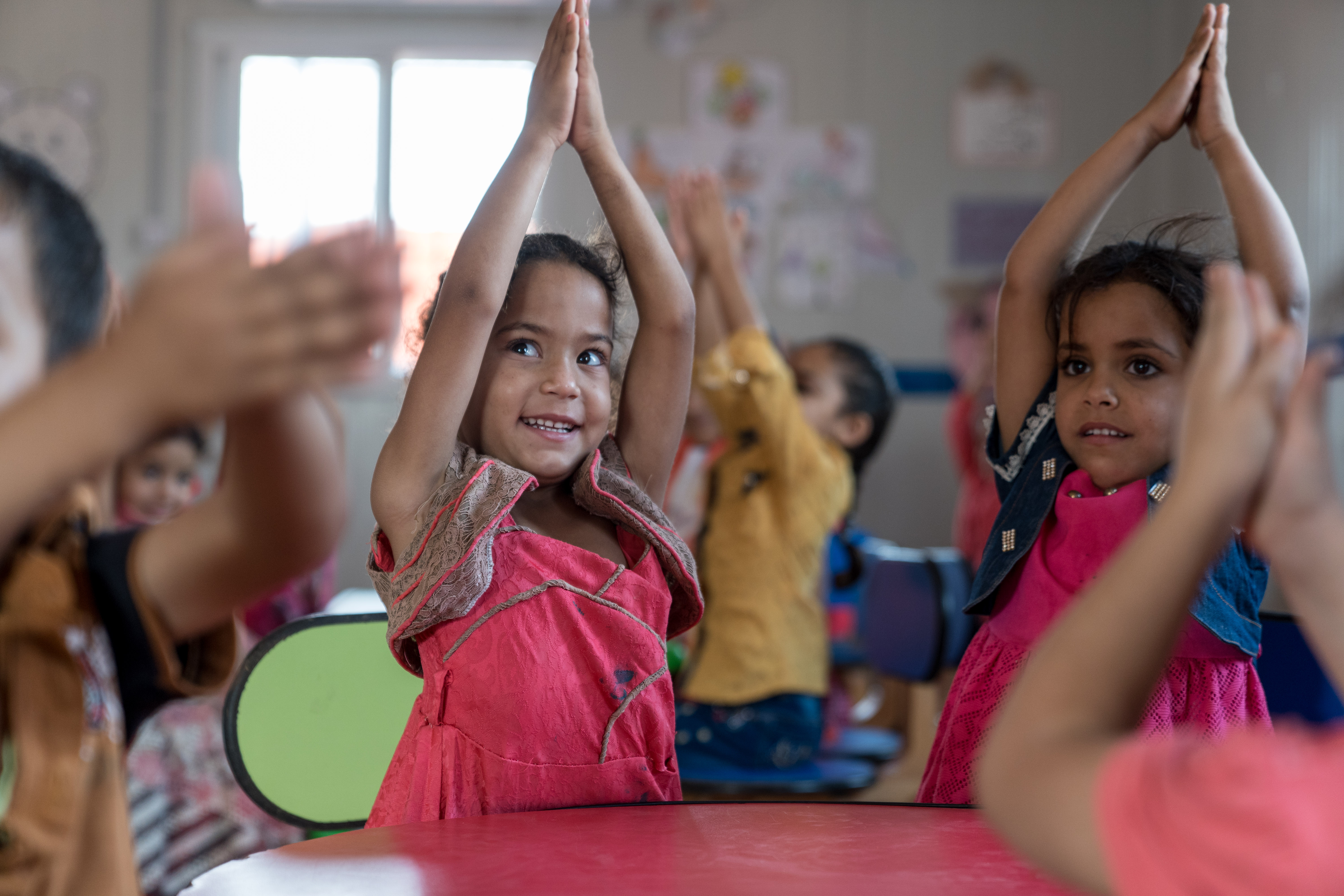 A child claps her hands above her head in a Kindergarten in Za'atari Refugee Camp