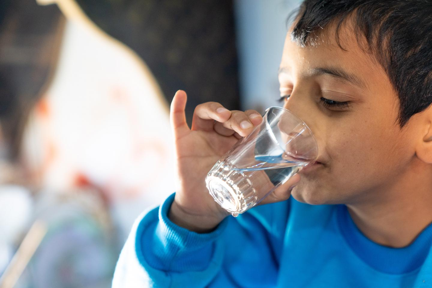 A boy drinks a glass of water