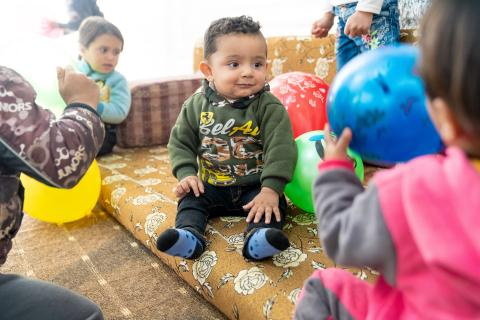 A baby boy sits surrounded by balloons and other children