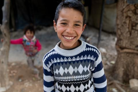 A boy standing outside smiles at camera