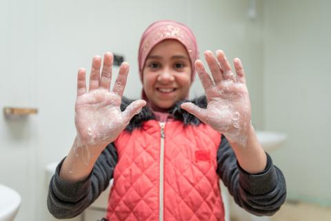 A girl shows her soapy hands