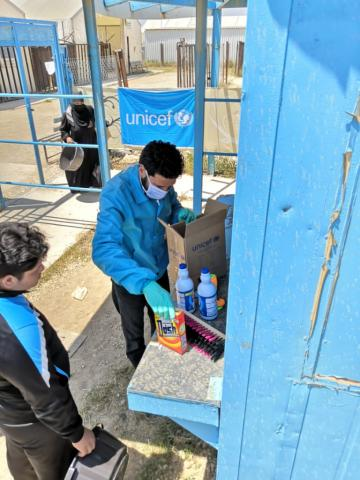 A UNICEF staff member packs a box with hygiene materials