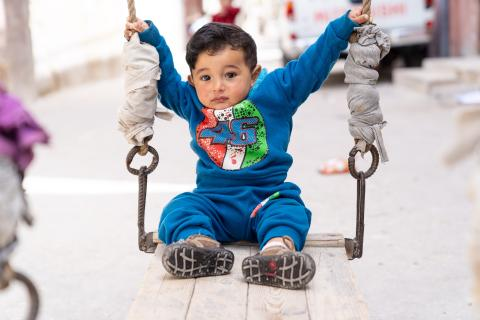 A boy on a swing on a street