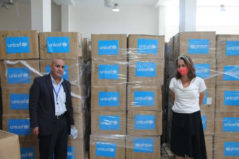 Two people stand apart with boxes in between