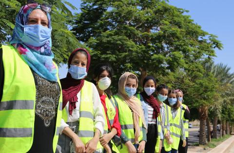Young volunteers wearing face masks line up