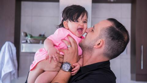 A father holds his infant daughter to his face