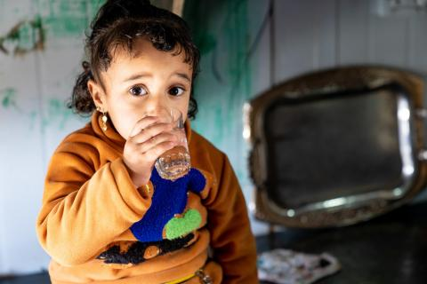Sham, 2 and a half years, drinks a glass of water given to her by her aunt Sidra, 14 in Za'atari Refugee Camp. Sham was born in the camp.