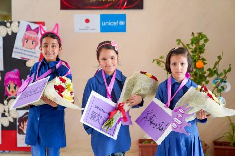 Three girl students line up holding flowers. The flag of Japan and UNICEF logo is in the background.