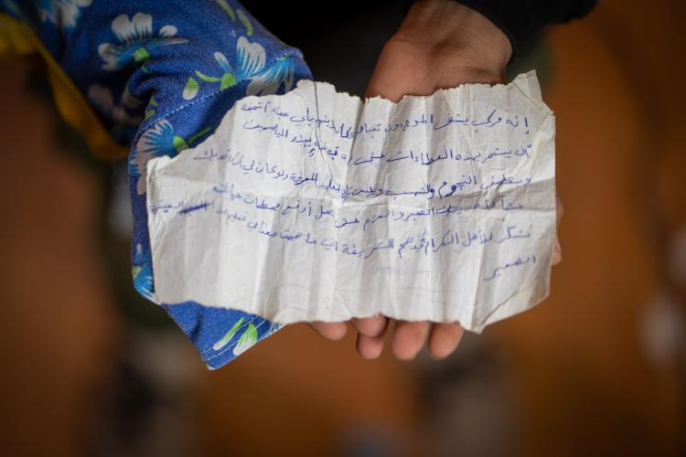 A handwritten note held in a boy's hands