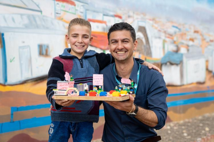 A boy and man hold a LEGO brick model