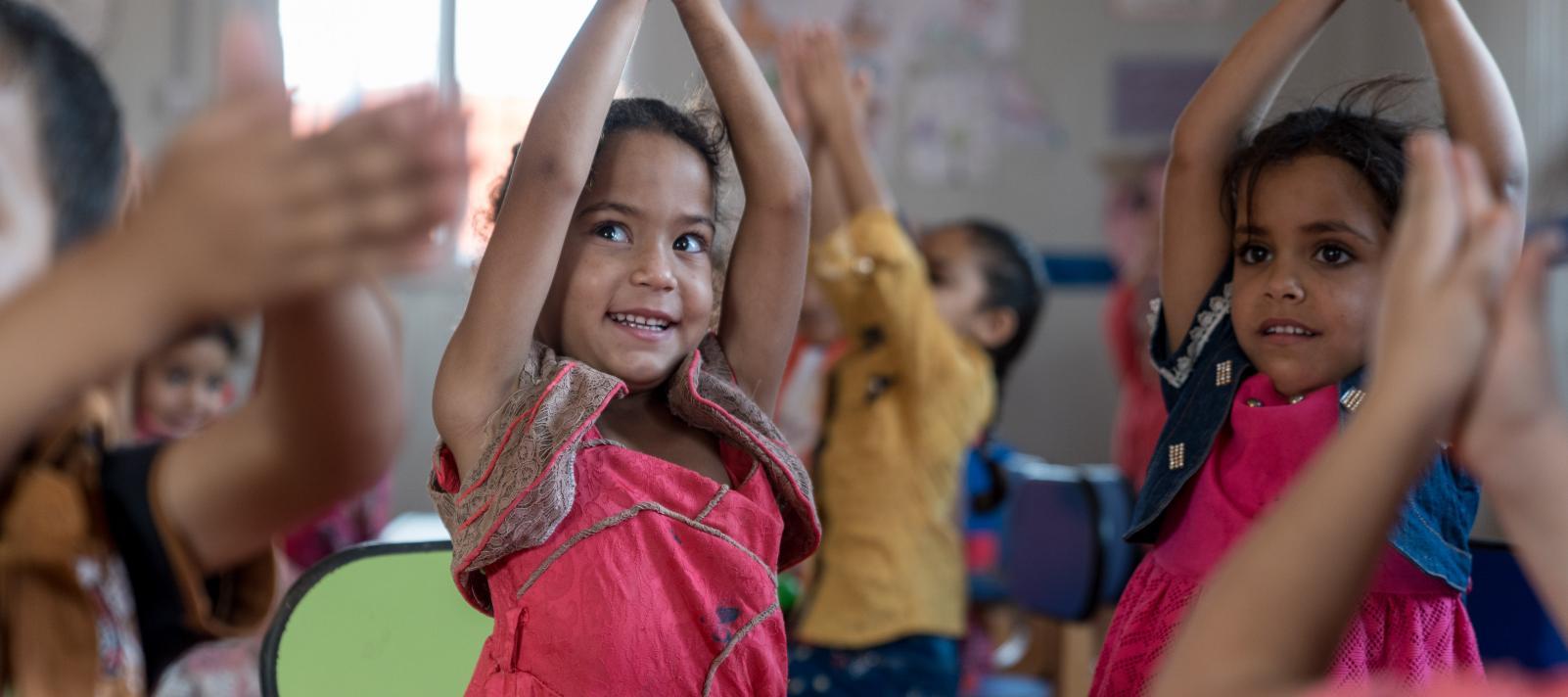 3bff9c082cfd4e A child claps her hands above her head in a Kindergarten in Za atari Refugee