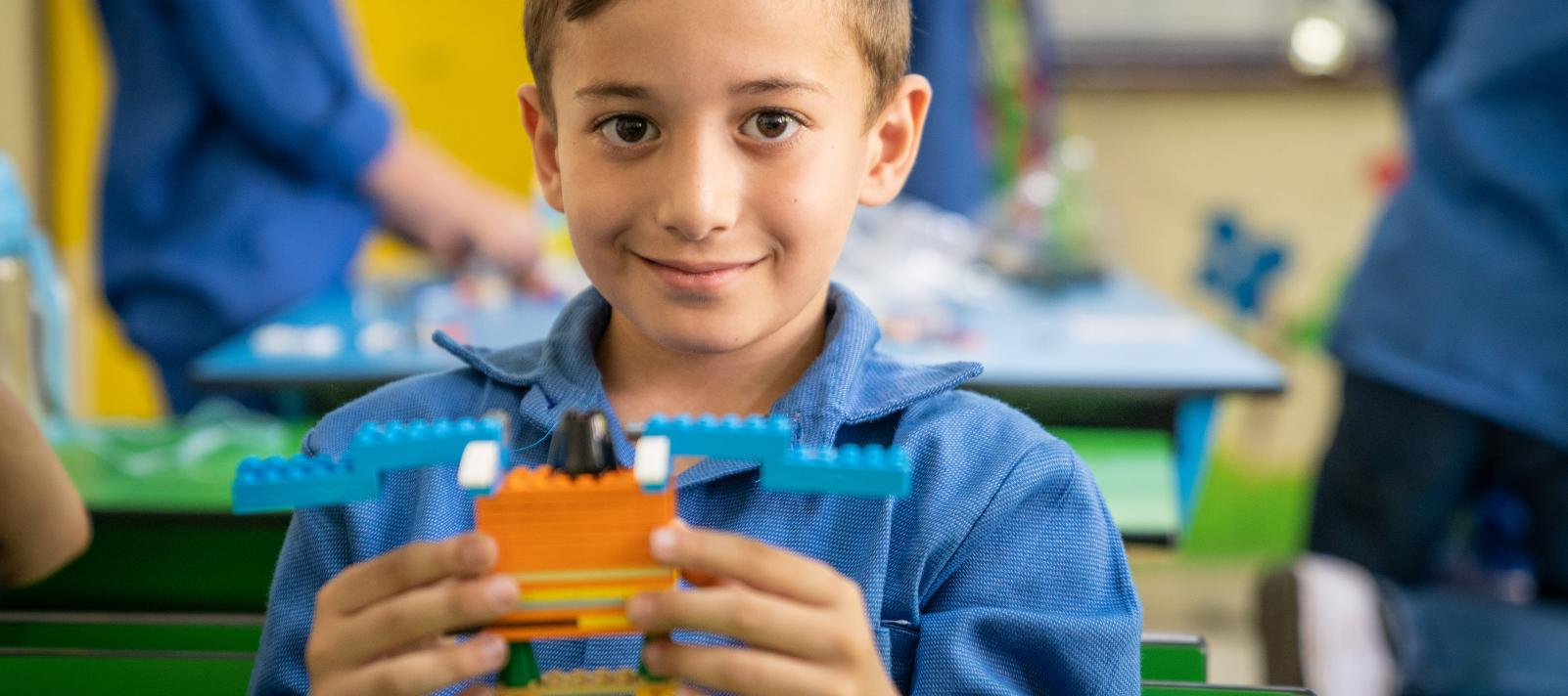 A boy holds his LEGO bricks creation in school