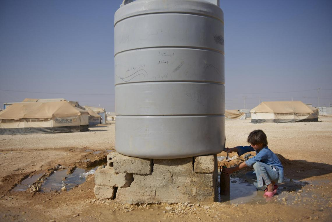 A child collects water from a water tank
