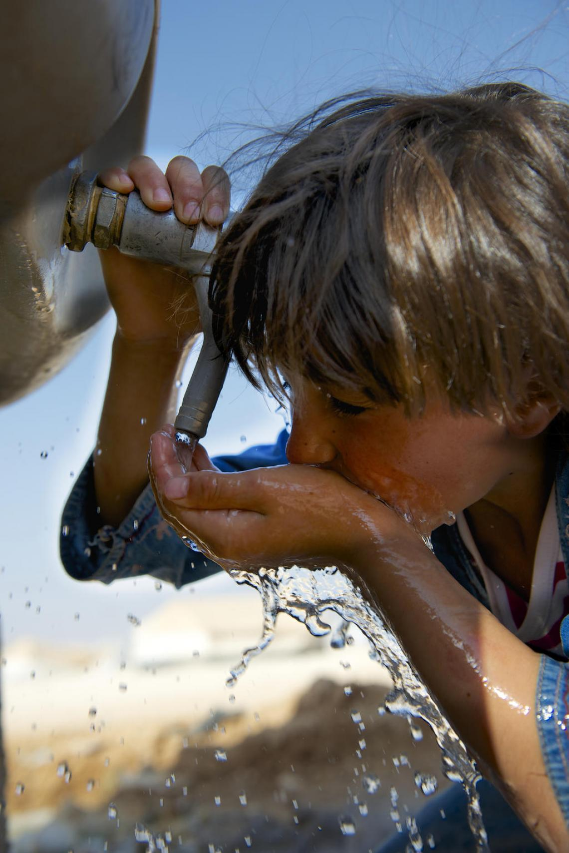 A child drinks water from a tap outside
