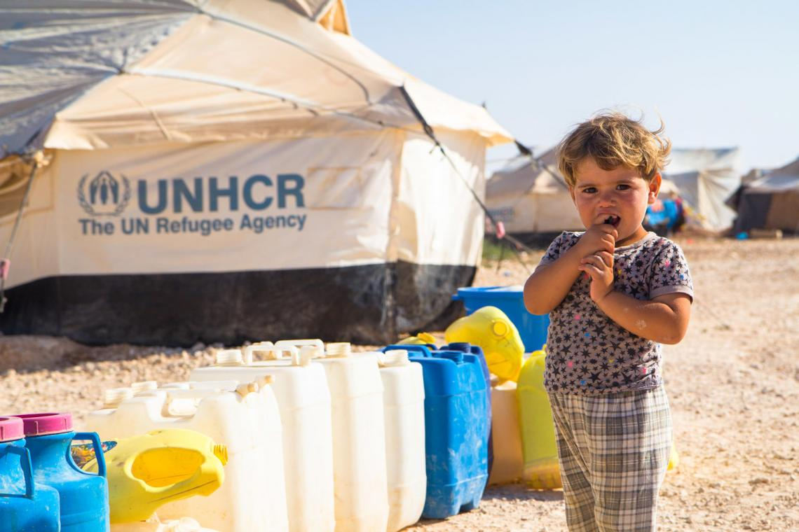 A girl stands next to jerrycans in a refugee camp