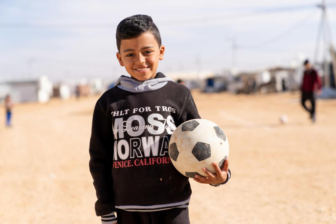 A boy stands outside holding a football