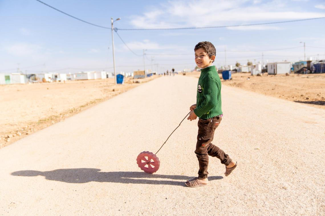 A boy plays with a wheel in a refugee camp