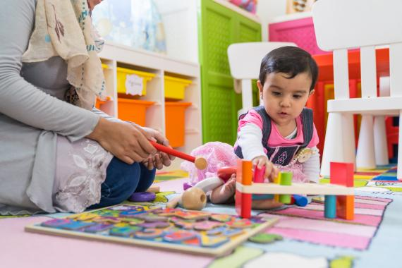 A girl child plays in a nursery beside her mother