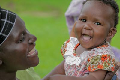 A mother plays with her daughter who is smiling.