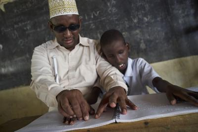 A visually-impaired teacher teaching a visually-impaired student to read with a braille book.