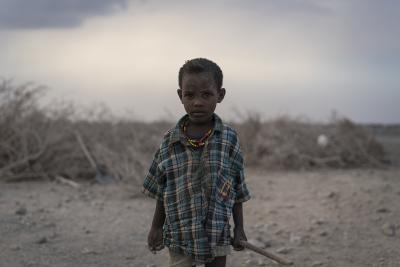 A young boy standing outside in a dry and dusty environment.