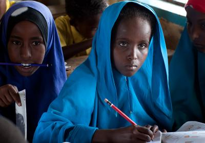 A muslim girl with a pencil in her hand seated in class.