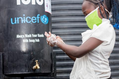 Girl washes hands in Mathare