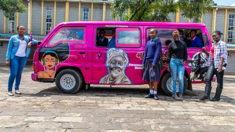 Girls stand next to a newly designed pubic van (matatu) created to celebrate women and girls.